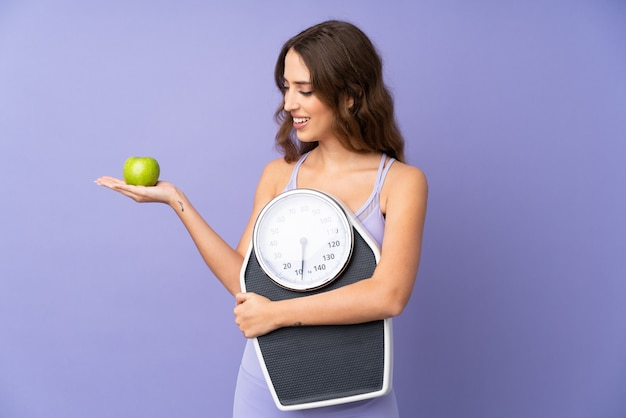 Young sport woman over purple wall holding a weighing machine while looking an apple
