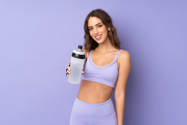 Young sport woman over purple wall with sports water bottle