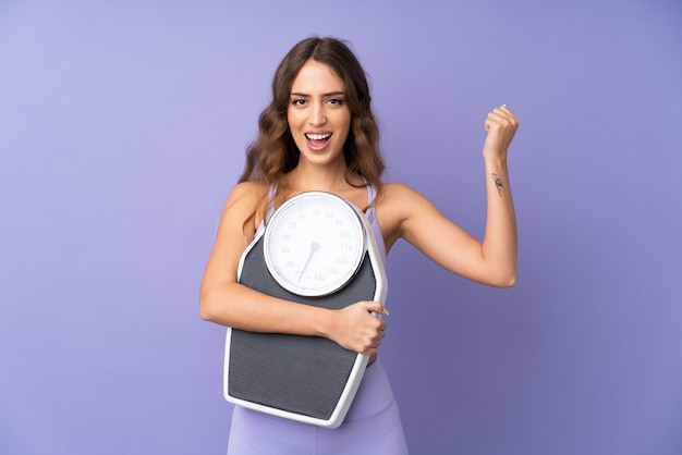 Young sport woman over purple wall with weighing machine and doing victory gesture