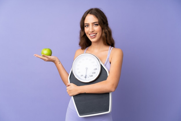 Young sport woman over purple wall with weighing machine and with an apple