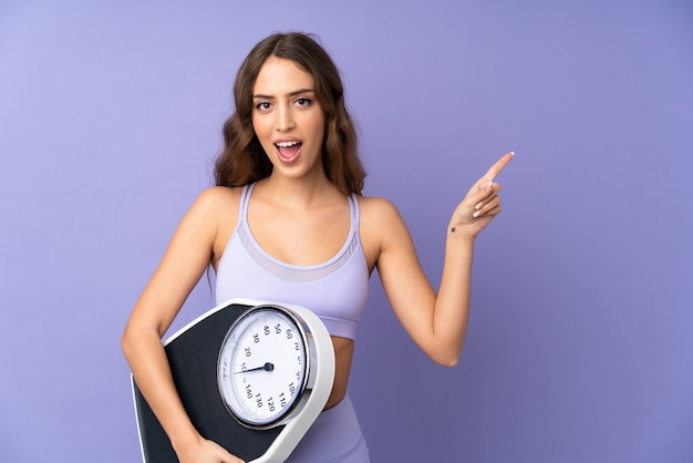 Young sport woman over purple wall with weighing machine