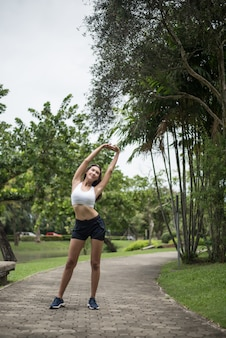 Young sport woman runner stretching body before run on track in the park.