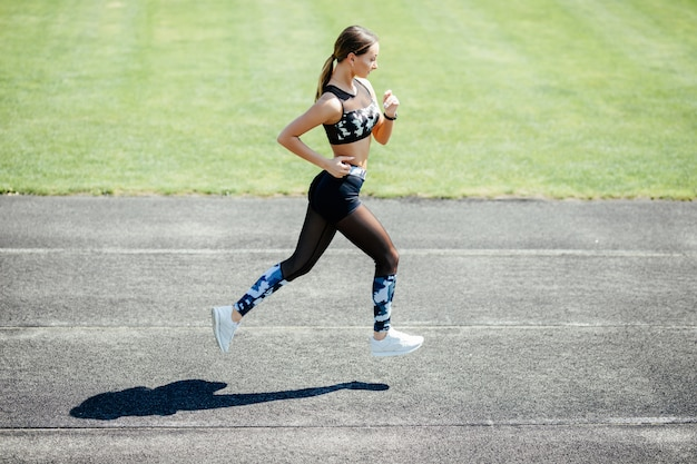 Young sport woman running at a track and field stadium