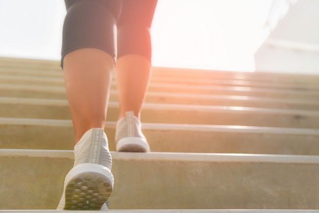 Young sport woman running up on stone stairs with sun spot background. workout and diet concept.