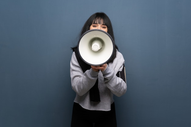 Young sport woman shouting through a megaphone