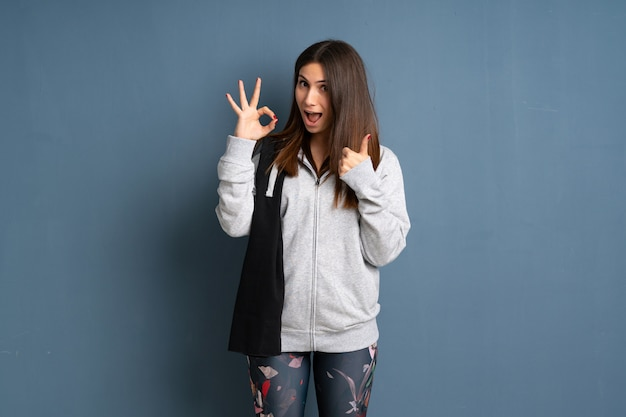 Young sport woman showing ok sign with and giving a thumb up gesture