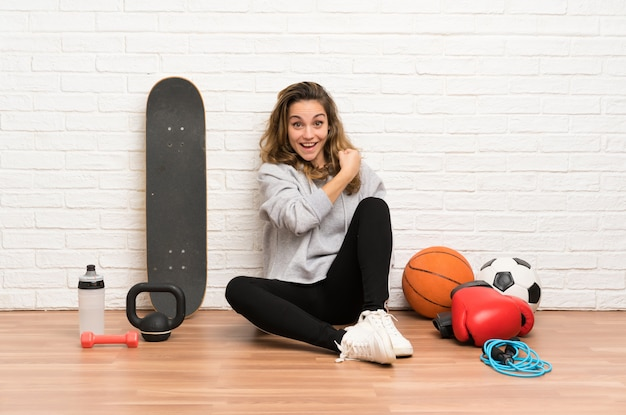Young sport woman sitting on the floor celebrating a victory