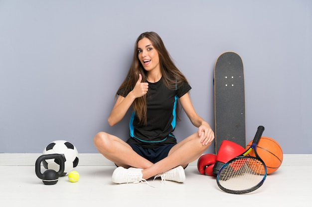 Young sport woman sitting on the floor giving a thumbs up gesture