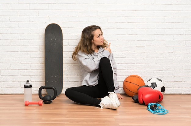 Young sport woman sitting on the floor pointing back with the index finger