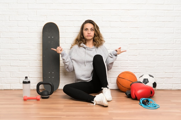 Young sport woman sitting on the floor pointing to the laterals having doubts
