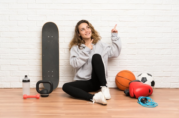 Young sport woman sitting on the floor pointing with the index finger a great idea