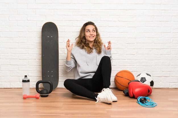 Young sport woman sitting on the floor with fingers crossing