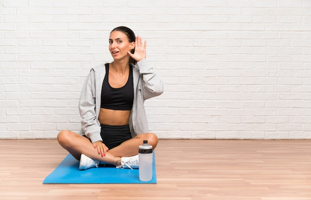 Young sport woman sitting on the floor with mat listening something