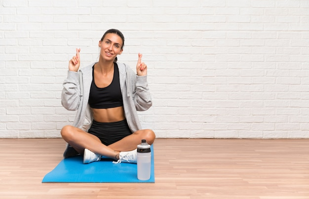 Young sport woman sitting on the floor with mat with fingers crossing