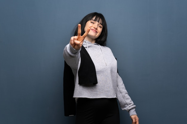 Young sport woman smiling and showing victory sign