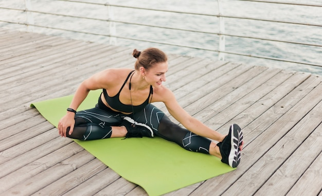 Young sport woman in sportswear does stretching one leg sitting on a mat on a wooden beach terrace