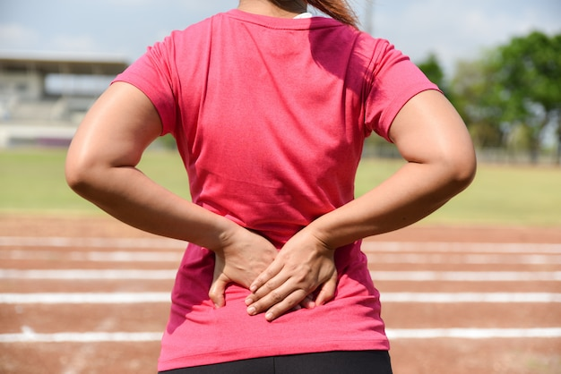 Young sport woman suffering from back pain, kidney inflammation, injury during workout, outdoors concept.