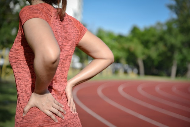 Young sport woman suffering from back pain