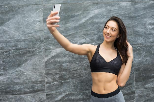 Молодая спортивная женщина делает селфи после занятий спортом на цветной стене на открытом воздухе