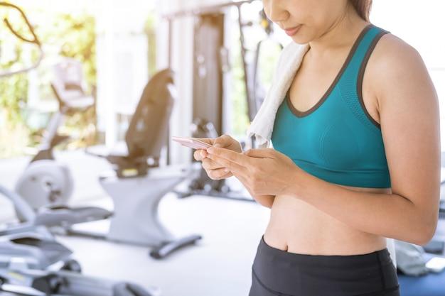 ジム、フィットネス、トレーニングライフスタイルのコンセプトでスマートフォンを使用して若いスポーツ女性