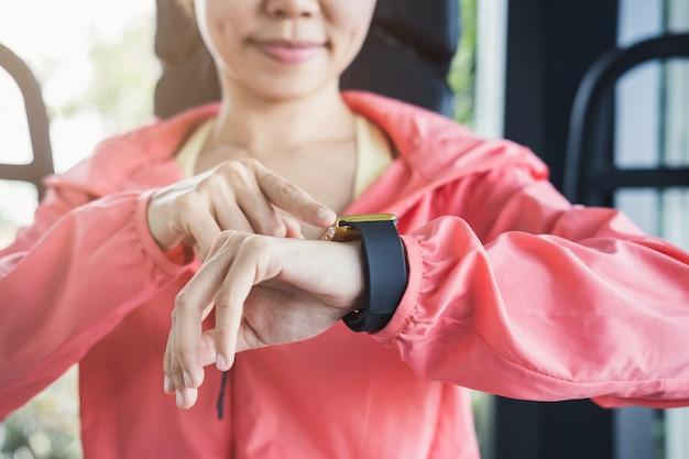 若いスポーツ女性のジムでスマートな腕時計を使用して
