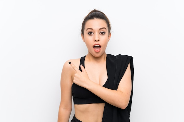 Young sport woman white wall surprised and pointing side