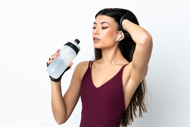 Young sport woman over white wall with sports water bottle