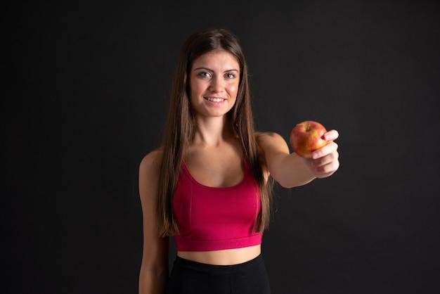 孤立した黒の上のリンゴと若いスポーツ女性