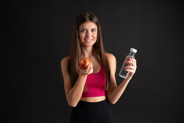 Young sport woman with a bottle of water over isolated black
