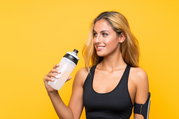 Young sport woman with a bottle of water over isolated wall