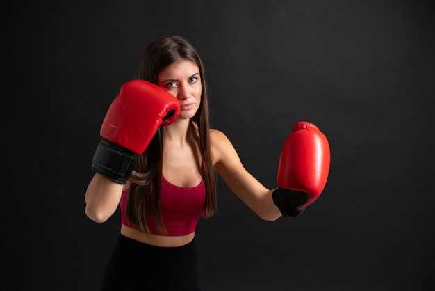 Young sport woman with boxing gloves over isolated black wall