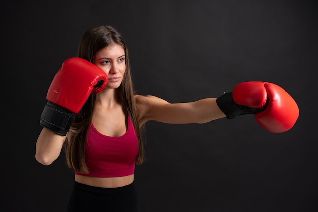Young sport woman with boxing gloves over isolated black