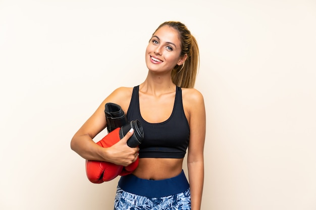 Young sport woman with boxing gloves over isolated wall