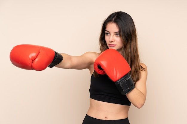 Young sport woman with boxing gloves over wall