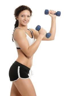 ダンベル、白い背景の上のフルレングスの若いスポーツの女性