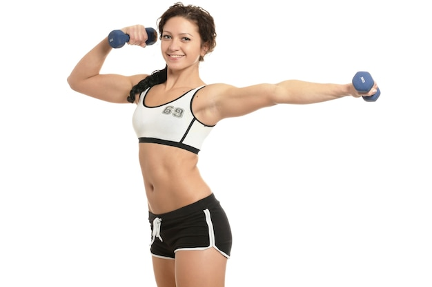 白い背景の上のダンベルと若いスポーツの女性