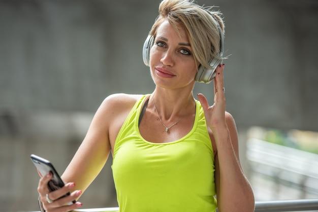 ハードワークアウト運動後のリラックスのための音楽を聴くイヤホンで若いスポーツ女性。