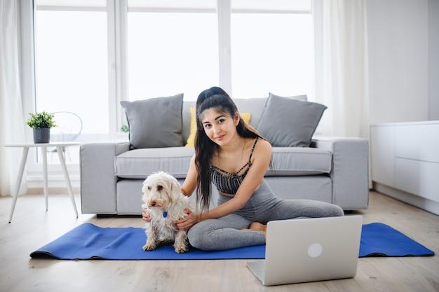 노트북과 개가 집에서 카메라를 보며 운동을 하는 젊은 스포츠 여성