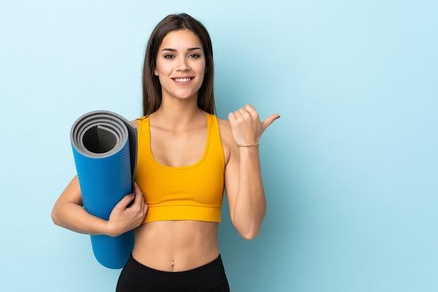 제품을 제시하기 위해 측면을 가리키는 파란색 배경에 고립 된 매트와 젊은 스포츠 여자