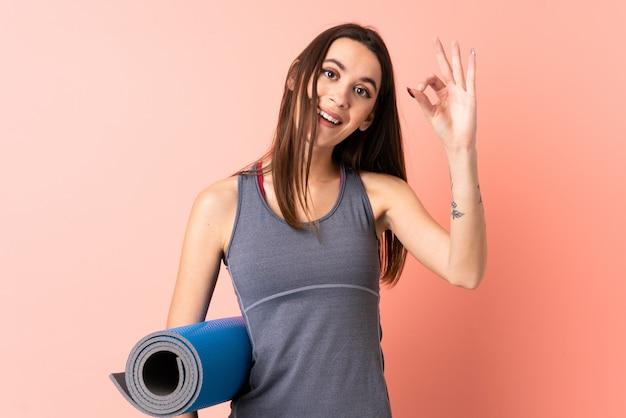 指でokの標識を示す分離の壁を越えてマットを持つ若いスポーツ女性