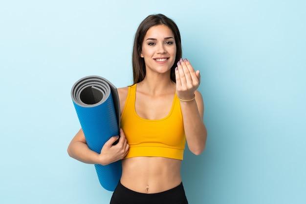 Молодая спортивная женщина с циновкой