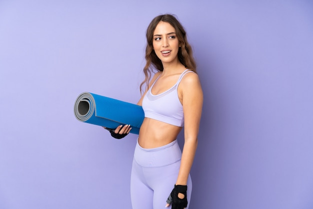 Young sport woman with a mat