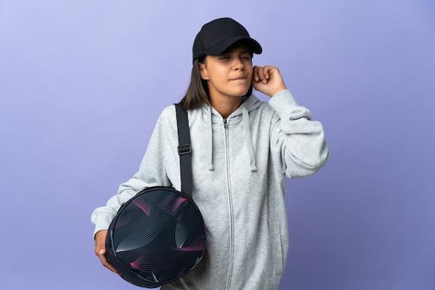 Молодая спортивная женщина со спортивной сумкой разочарована и закрывает уши
