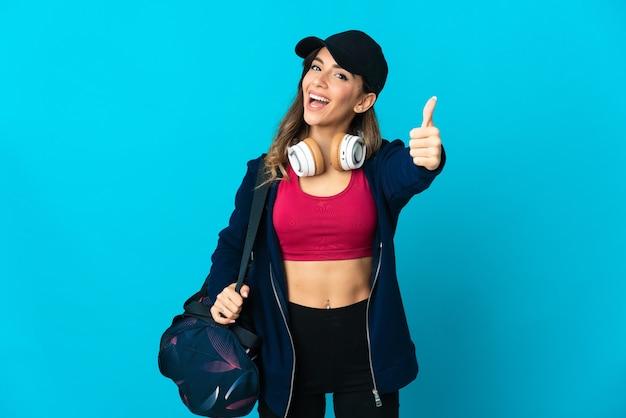 좋은 일이 일어났기 때문에 엄지 손가락으로 파란색 배경에 고립 된 스포츠 가방을 가진 젊은 스포츠 여자