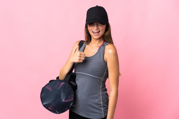 제스처를 엄지 손가락을주는 분홍색에 고립 된 스포츠 가방 젊은 스포츠 여자