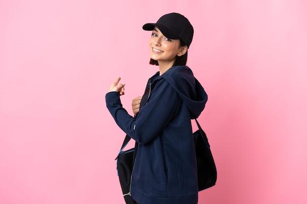 다시 가리키는 분홍색에 고립 된 스포츠 가방 젊은 스포츠 여자