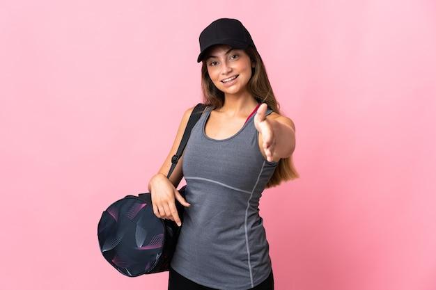 Молодая спортивная женщина со спортивной сумкой, изолированной на розовом, трясет руками для заключения хорошей сделки