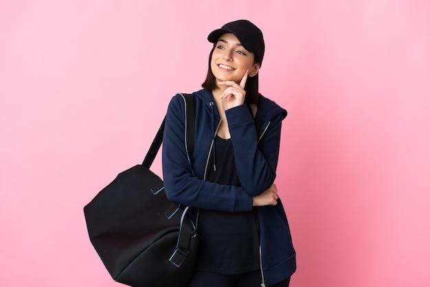 Молодая спортивная женщина со спортивной сумкой изолирована на розовом, думая об идее, глядя вверх