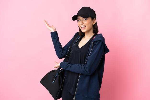 ピンクの壁に隔離されたスポーツバッグを持つ若いスポーツの女性は、来て招待するために手を横に伸ばします