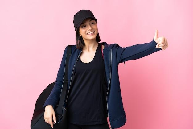 親指を立てるジェスチャーを与えるピンクの壁に分離されたスポーツバッグを持つ若いスポーツ女性